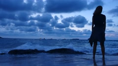 Young female standing and watching ocean waves on the beach after sunset. Stock Footage
