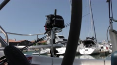 Small motor attached to stern of sail boat view aft from cockpit at dock with Stock Footage