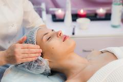 Beautiful young woman relaxing with face massage at beauty spa Stock Photos