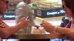 Couple continuously tapping their mobile phone touchscreens in a cafe. Mobile Stock Footage