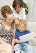 Child and his mother with grandmother play with tablet Stock Photos