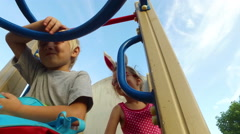 Girl with ears and glasses and boy with white hair having fun on the children's Stock Footage