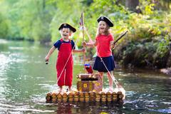 Kids playing pirate adventure on wooden raft Stock Photos