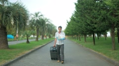 Young man tourist is with a large suitcase on wheels around the city park. In Stock Footage