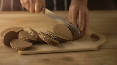 Hands cutting bread with knife on rustic wooden table Stock Footage