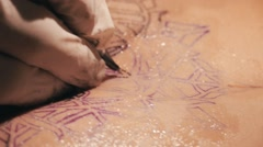 Tattoo master making a tattoo of mandala pattern. Close up shot of hands Stock Footage