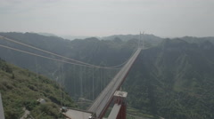 Aerial slider shot of a suspension bridge across a valley in China Stock Footage
