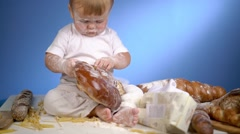 Baby baker playing with bread in flour Stock Footage