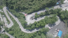 Drone shot of traffic driving over winding mountain road in China Stock Footage