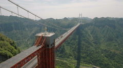 Aerial shot flying towards suspension bridge in mountain landscape China Stock Footage