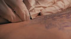 Tattoo master making a tattoo of mandala pattern. Close up shot of hands Stock Footage