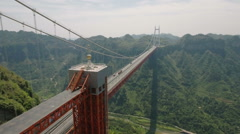 Aerial view of suspension bridge spanning mountain valley in China Stock Footage