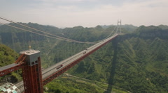 Aerial drone shot flying towards impressive Aizhai suspension bridge in China Stock Footage