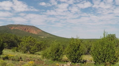 Side View Car Driving By Red Mountain Volcanic Crater- Flagstaff AZ Stock Footage