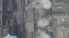 Overhead flight over reactors of steel factory billowing smoke in China Stock Footage