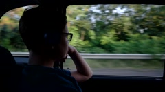 Young Boy Sits in the Car and Listens Music Through the Headphones While Stock Footage