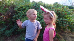 Girl with ears and glasses and boy with white hair standing near the bush and Stock Footage