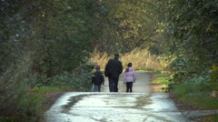 Old Man With 2 Grand Children Walking Down the Road in the Forest. Back View Stock Footage
