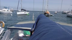 View of other moored yachts along boom of sailboat looking stern over dodger. Stock Footage