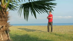 The man on the rocky beach. Palm tree in the foreground. The man responsible for Stock Footage