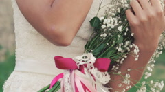 Happy bride embracing bouquet and looking aside. Slowly Stock Footage