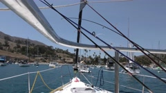 Yachts at anchor in Two Harbors Catalina fishing rods in foreground seen from Stock Footage
