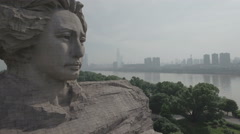 Tilting rising aerial shot of a statue of a young Mao Zedong in China Stock Footage