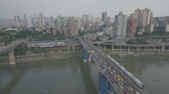 Aerial view of commuter metro train riding past traffic jam in Chongqing Stock Footage