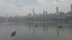 Flying over traditional wooden fishing boats to modern skyline Chongqing China Stock Footage