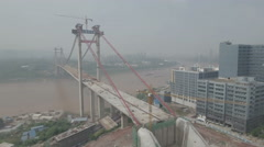 Aerial panning shot new bridge under construction, Yangtze river Chongqing China Stock Footage