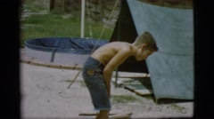 1968: young man stoking the fire to keep the campfire burning COTTONWOOD, Stock Footage