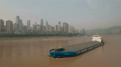 Aerial drone shot cargo vessel sailing on Yangtze river, Chongqing skyline China Stock Footage