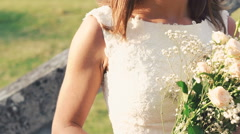 Close up of bride smelling bouquet, smiling and looking on sun. Slowly Stock Footage