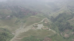 Sweeping panoramic aerial view of village in green rice terraces China Stock Footage