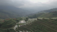 Aerial drone flight over green rice terraces small village in rural China Asia Stock Footage