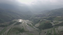 Aerial drone flight over rice terrace fields, threatening clouds in rural China Stock Footage