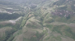 High angle aerial footage of rice terrace fields and a small village in China Stock Footage