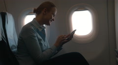 In cabin of plane girl sitting on chair and using mobile terminal on phone and Stock Footage