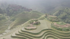 Beautiful aerial drone view of green rice terrace fields and village in China Stock Footage