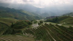 Breaking clouds revealing sunlight rice terraces mountain scenery China Stock Footage