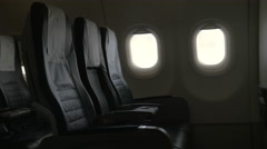 Seen interior decor of plane - black leather chairs and two portholes Stock Footage
