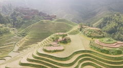 Flying over scenic green rice fields towards mountain village in China Stock Footage