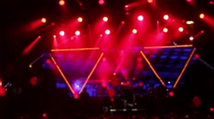 Defocus silhouettes of concert crowd in front of bright stage lights Stock Footage