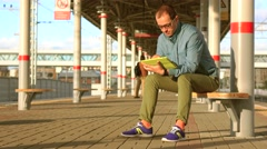 Bald nerdy man in glasses sitting at railroad station and using his tablet Stock Footage
