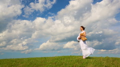 Regnant woman with toy bear on the field Stock Footage