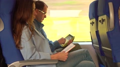 Couple travelling by train. Girl reading a book and man using his tablet Stock Footage