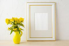 Frame mockup with small yellow flowers in stylized pitcher vase Stock Photos