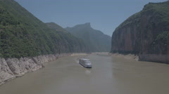 Panning aerial shot of cruise ship sailing through Three Gorges in China Stock Footage