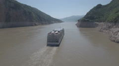 Flying behind a commercial cruise ship sailing over the Yangtze river China Stock Footage