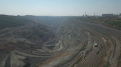 Aerial drone flight over a massive (almost depleted) open coal mine pit in China Stock Footage